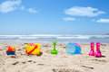 Colorful plastic toys and gumboots on beach sand with sea in background Stock Photos