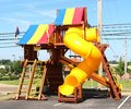 Colorful plastic and wood children s playground with blue yellow red rainbow awning Royalty Free Stock Photos