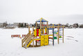 Colorful playground frozen snowy lake house winter on bank shore and living district on other shore in Stock Images
