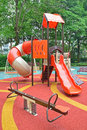 Colorful playground structure with plenty of games for kids the include slides climbers playhouse seesaw and swing Stock Images