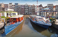 Colorful pleasure boats stand moored on damrak canal amsterdam netherlands march pier in historical center of amsterdam Royalty Free Stock Images