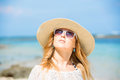 Colorful portrait of young pretty girl at the in sunglasses and a hat relaxing near sea and enjoying her summer vacation travel Royalty Free Stock Photography