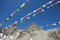 Colorful prayer flags and mountain peak against blue sky glacier Stock Photo