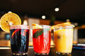 Colorful punch drinks on bar close up three glasses with fruit sangria blurred restaurant background free space refreshment party Royalty Free Stock Images