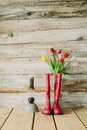 Colorful rain boots with spring flowers and oli lamp in wooden b