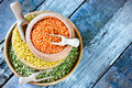 Colorful raw cereals in wooden bowls red lentils green peas bulgur space for text Royalty Free Stock Photo