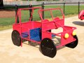 Colorful red blue and yellow toy car buggy on childrens playground black school Stock Photography