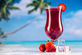 Colorful red cold drink on a beach, summer background Royalty Free Stock Photo