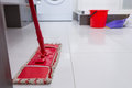Colorful red mop on a clean white tiled floor Royalty Free Stock Photo