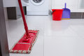 Colorful red mop on a white tiled floor Royalty Free Stock Photo