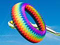 Colorful ring kite flying in a bright blue sky at the long beach kite festival Stock Images