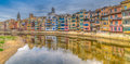 Colorful river front houses of all shapes and sizes painted in various ochre yellow red tones lining the onyar girona Stock Image