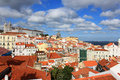Colorful rooftops and houses in alfama lisbon portugal under a scattered cloudy sky Royalty Free Stock Images