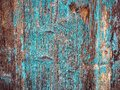 Colorful rough wood texture: old rustic house wall covered with bright turquoise peeling paint.