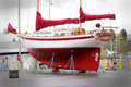 Colorful sailboat in dry dock a red sits for repair and maintenance Royalty Free Stock Photo