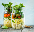 Colorful salad with couscous, tofu and vegetables in a jar.