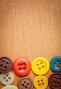 Colorful sewing buttons on a wooden background Royalty Free Stock Photography