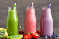 Colorful smoothie drinks in bottles with a straw and fresh fruits and berries Royalty Free Stock Photo