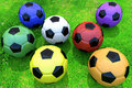 Colorful soccer balls on grass Royalty Free Stock Photos