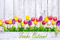 Colorful spring tulips on wooden background for easter Stock Photo