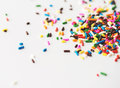 Colorful sprinkles a pile of and edible scattered on a white tabletop Royalty Free Stock Photos