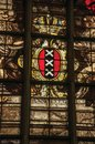 Colorful stained glass window inside the gothic old church with the coat of arms of Amsterdam.