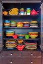 Colorful Stoneware Dinnerware in China Cabinet Royalty Free Stock Photo