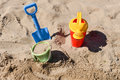 Colorful summer beach toys, bucket, sprinkler and shovel on sand Royalty Free Stock Photo