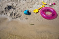 Colorful swim ring life buoy, bucket and shovels on the beach Royalty Free Stock Photo