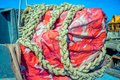 Colorful tarpaulin material and old thick rope Royalty Free Stock Photo