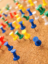 Colorful thumbtacks on cork board Royalty Free Stock Images