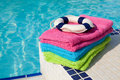 Colorful towels and life buoy near the swim pool Royalty Free Stock Photo