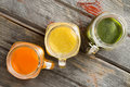 Colorful trio of fresh fruit juice in glass jugs Royalty Free Stock Photo