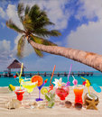 Colorful tropical cocktails at beach on white sand and palm tree Royalty Free Stock Photos