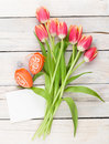 Colorful tulip bouquet easter eggs and blank greeting card top view over white wooden table Stock Photos