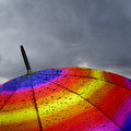 Colorful umbrella top with raindrops and heavy clouds Stock Image