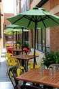 Colorful umbrellas offering shade at outdoor restaurant big over tables set for diners Royalty Free Stock Images