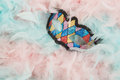 Colorful venetian carnival mask lying in blue and pink pastel colored feathers Royalty Free Stock Photo