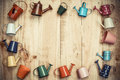 Colorful watering cans and buckets small arranged as a picture frame on wood plank background Stock Photography