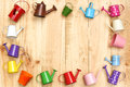 Colorful watering cans and buckets small arranged as a picture frame on wood plank background Stock Photo