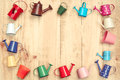Colorful watering cans and buckets small arranged as a picture frame on wood plank background Stock Photos