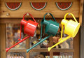 Colorful watering cans hung outside the window Royalty Free Stock Photo