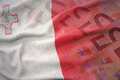 Colorful waving national flag of malta on a euro money banknotes background. Royalty Free Stock Photo