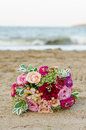 Colorful wedding bouquet from roses. Pink, red and green. Beach wedding. Royalty Free Stock Photo