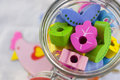 Colorful wooden beads in shape of flowers and leaves in transparent glass jar Royalty Free Stock Photo