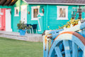 Colorful wooden bungalow with old blue wooden wagon. Royalty Free Stock Photo