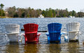 Colorful wooden chairs in a lake on submerged dock during flood Royalty Free Stock Photos