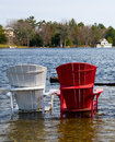 Colorful wooden chairs in a lake on submerged dock during flood Royalty Free Stock Images