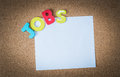 Colorful Wooden word JOBS with White paper on cork board
