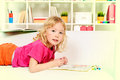 Coloring book cute little girl lying on a sofa at home and drawing Stock Photo